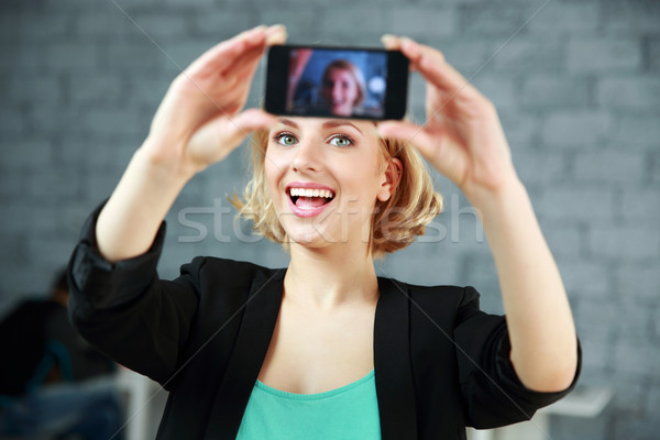 Young laughing woman making a self photo by her smartphone in office Stock photo © deandrobot