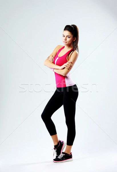 Full-length portrait of a young beautiful woman standing with arms folded on gray background Stock photo © deandrobot
