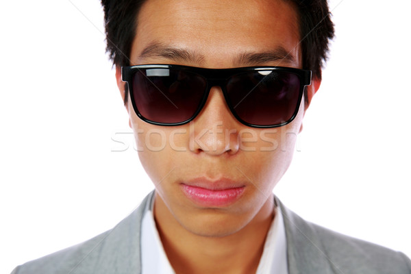 Closeup portrait of a serious asian man in sunglasses over white background Stock photo © deandrobot