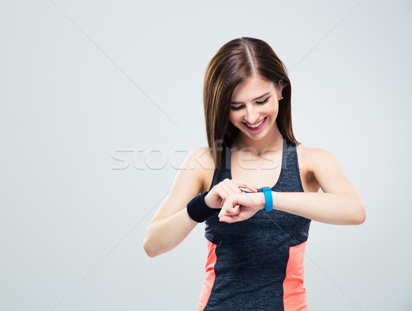 Happy young woman using activity tracker Stock photo © deandrobot