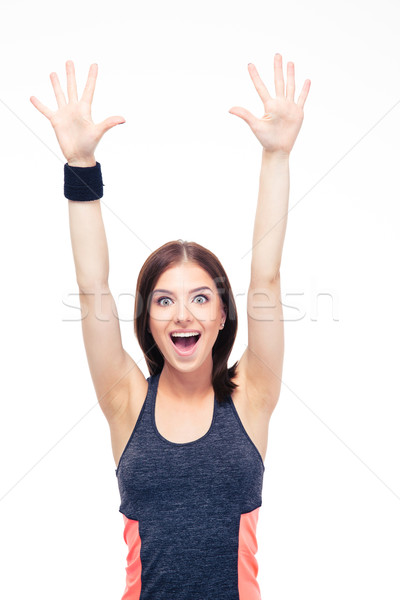 Laughing fitness woman standing with raised hands up Stock photo © deandrobot