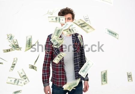 Smiling man throwing money into air over gray background Stock photo © deandrobot
