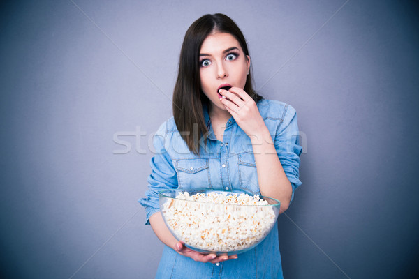 Young surprised woman eating popcorn Stock photo © deandrobot