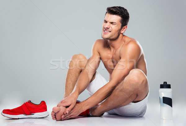Portrait of a fitness man with foot pain Stock photo © deandrobot