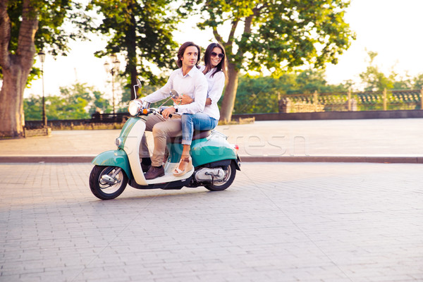 Sideview of a trendy couple riding a scooter in the morning Stock photo © deandrobot