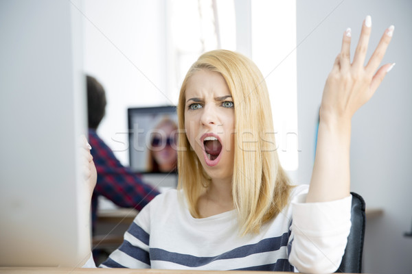 Shocked young woman working on computer Stock photo © deandrobot