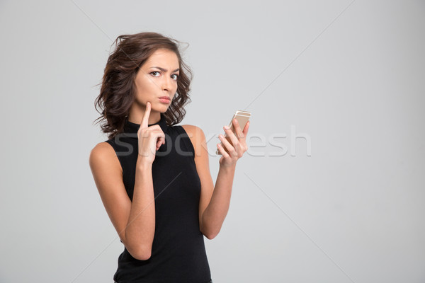 Annoyed young woman using cellphone Stock photo © deandrobot