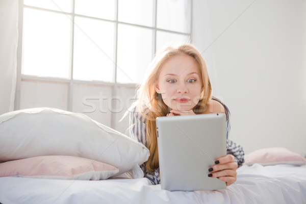 Surprised  woman lying in bed and using tablet PC Stock photo © deandrobot