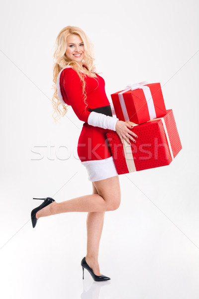 Attractive happy woman in red santa claus costume holding presents  Stock photo © deandrobot