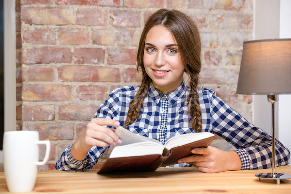 Smiling woman sitting at the table with book Stock photo © deandrobot