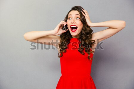 Happy amazed woman in red dress talking on the phone Stock photo © deandrobot