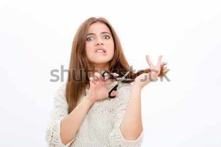 Unsure doubting pretty young woman cutting her hair Stock photo © deandrobot