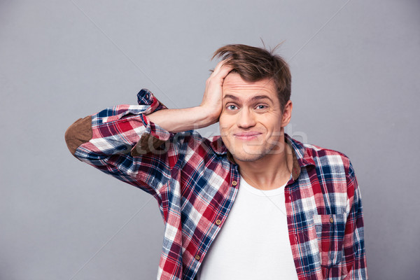 Close up of embarrassed man scratching head and looking confused  Stock photo © deandrobot