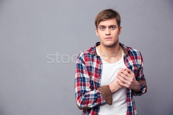 Stunned dazed man in checkered shirt with hand on chest Stock photo © deandrobot