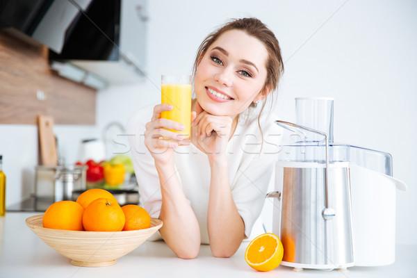 Beautiful smiling woman drinking fresh orange juice  Stock photo © deandrobot
