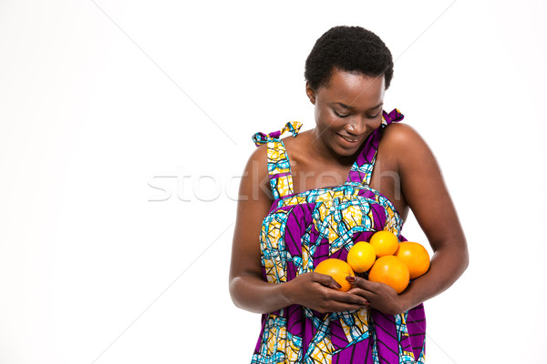 Happy african woman in bright sundress with oranges and lemons  Stock photo © deandrobot