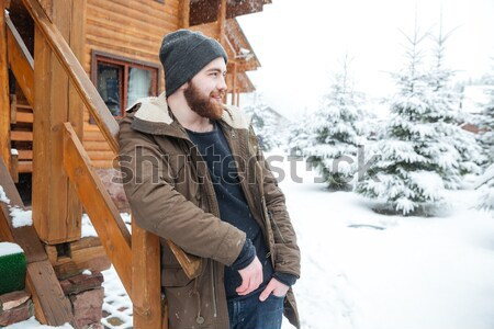 Smiling man standing and enjoying  snowy weather on winter resort Stock photo © deandrobot