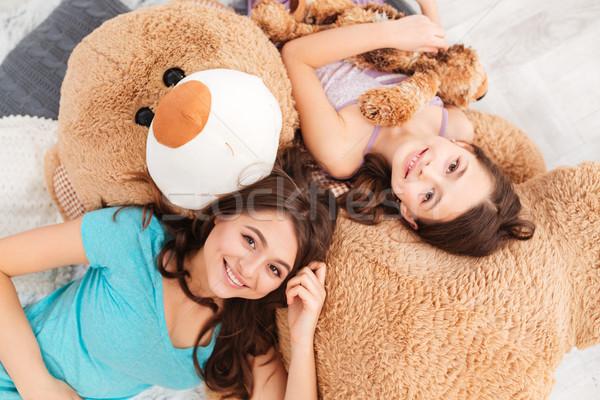 Two smiling beautiful sisters lying on big soft plush bear Stock photo © deandrobot