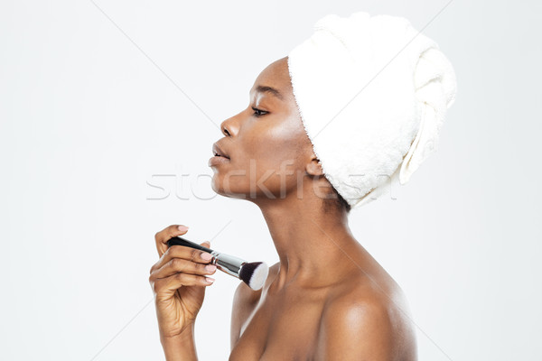 Afro american woman applying makeup with brush Stock photo © deandrobot