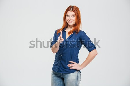 Frowning annoyed redhead young woman with hands on waist  Stock photo © deandrobot