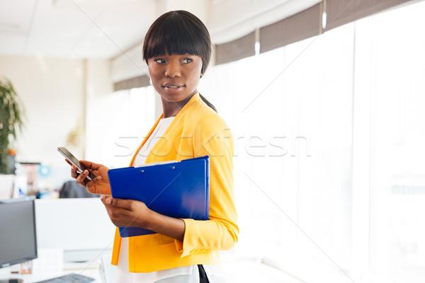 Сток-фото: афро · американский · деловая · женщина · папке · смартфон