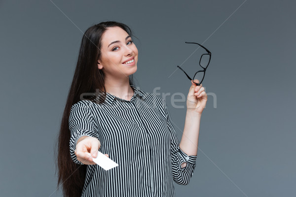 Happy businesswoman giving blank card at camera Stock photo © deandrobot