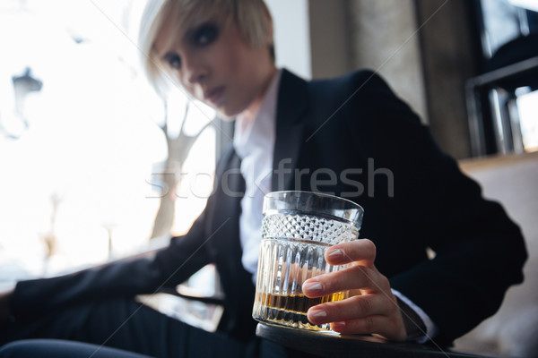 Young attractive blonde girl with frustrated look holding glass Stock photo © deandrobot