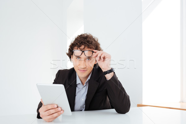 Businessman sitting at the table with tablet computer  Stock photo © deandrobot