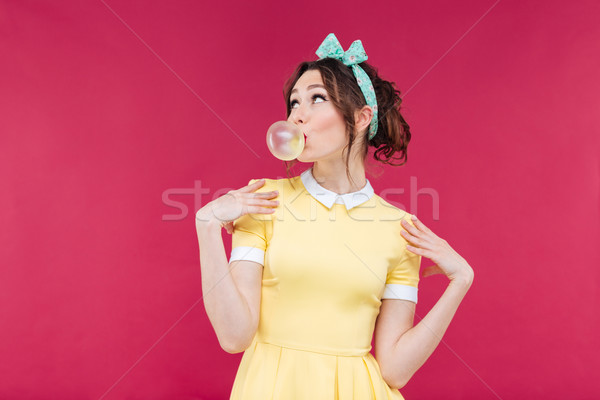 Thoughtful attractive young woman blowing bubble from chewing gum Stock photo © deandrobot