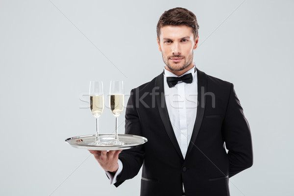 Butler in tuxedo holding tray with two glasses of champagne Stock photo © deandrobot