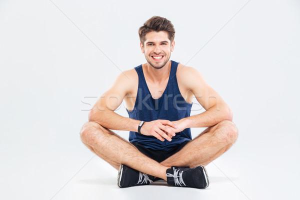Derűs fiatalember atléta ül lábak keresztbe fehér Stock fotó © deandrobot