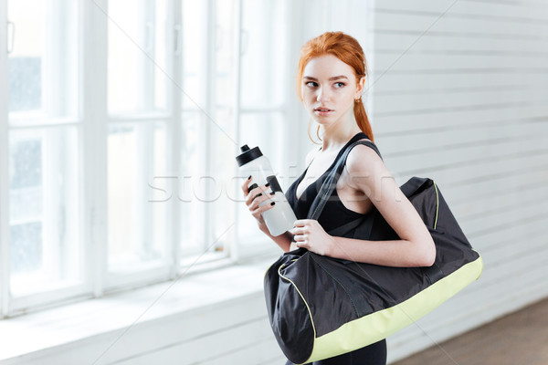 Stock photo: Young woman with bottle of water and sports bag