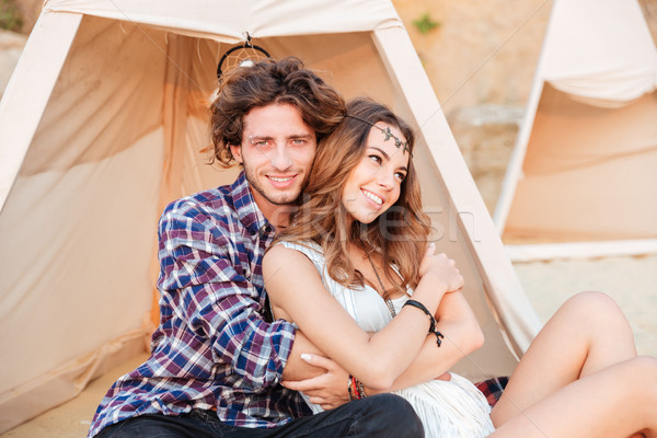 Couple sitting and embracing in teepee on the beach Stock photo © deandrobot