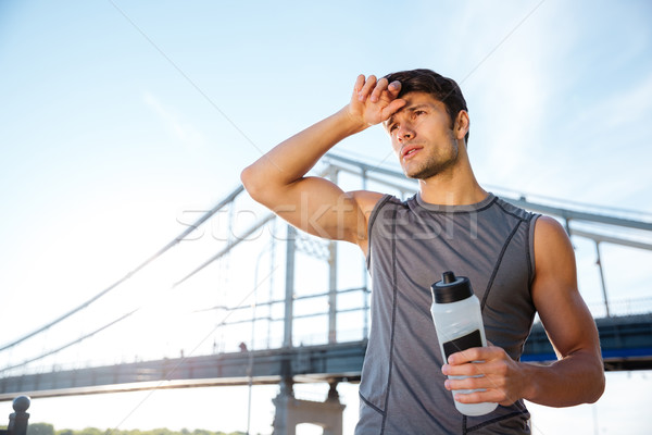 Young sports man resting after running and holding water bottle Stock photo © deandrobot