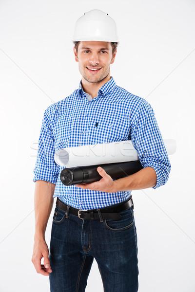 Derűs férfi építész védősisak áll tart Stock fotó © deandrobot