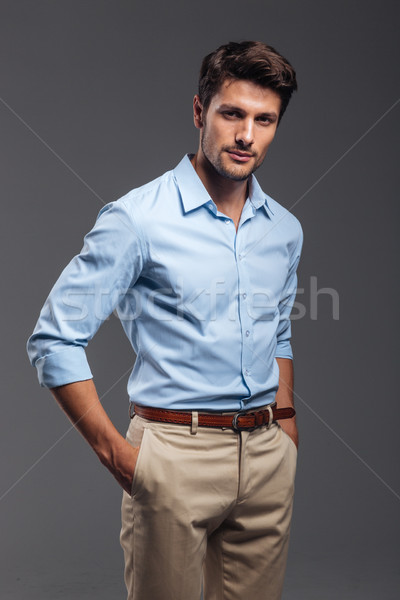 Handsome young man standing with hands in pockets Stock photo © deandrobot