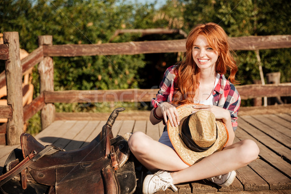 Happy woman cowgirl with hat sitting on ranch Stock photo © deandrobot