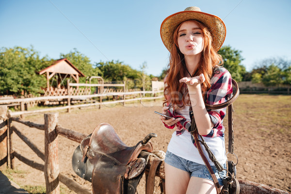 Pretty redhead cowgirl in straw hat sending air kiss Stock photo © deandrobot