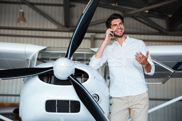 Stock photo: Man standing and talking on mobile phone near the plane