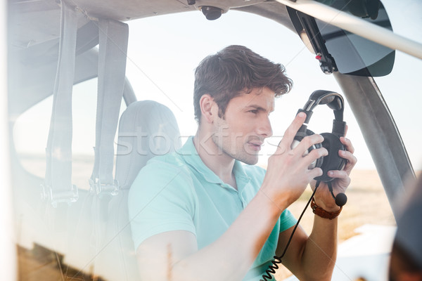 Man pilot in cabin of small aircraft Stock photo © deandrobot