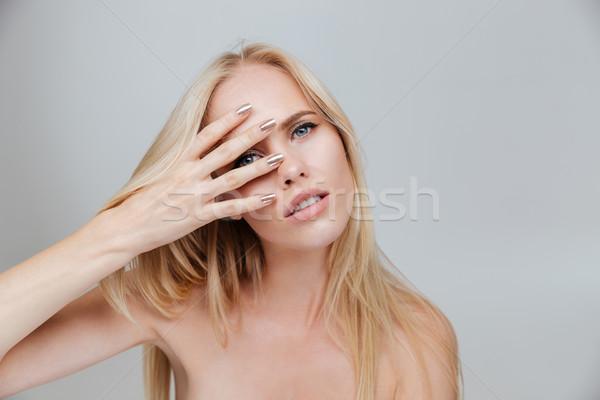 Gülen sarışın kadın bakıyor kamera parmaklar yalıtılmış Stok fotoğraf © deandrobot