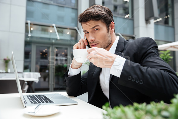 Businessman with laptop talking on mobile phone and drinking coffee Stock photo © deandrobot