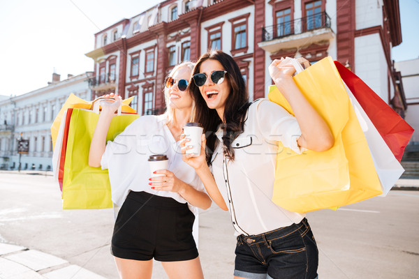 Two happy women holding shopping bags and having fun laughing Stock photo © deandrobot