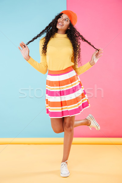Cheerful playful african young woman in bright clothes and hat Stock photo © deandrobot