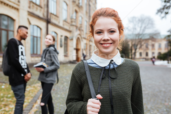 Redhead woman student with backpack standing outside at the campus Stock photo © deandrobot