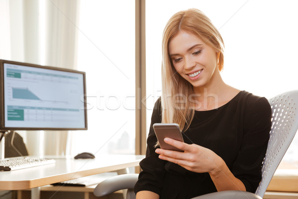 Happy young woman worker chatting by phone Stock photo © deandrobot
