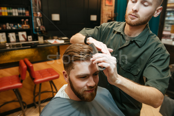 Young hipster man getting haircut by hairdresser Stock photo © deandrobot