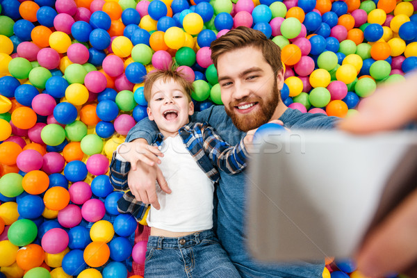 Boy and his father taking selfie in pool with balls Stock photo © deandrobot
