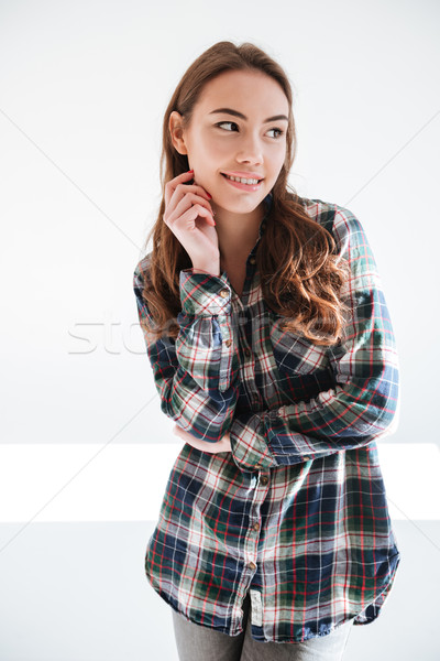 Smiling playful young woman in plaid shirt standing Stock photo © deandrobot