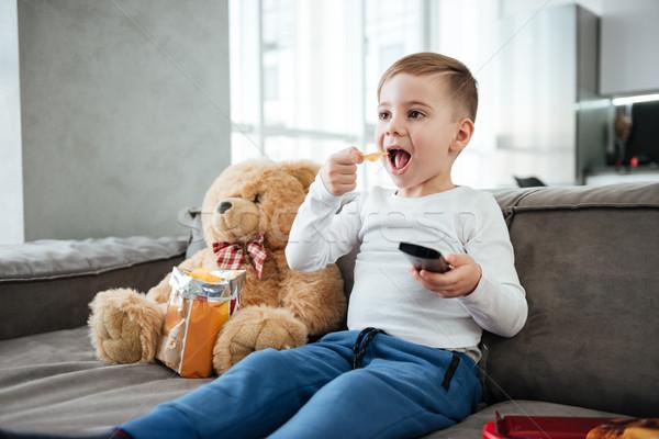 Little happy boy sitting on sofa with teddy bear Stock photo © deandrobot